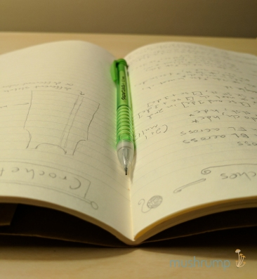 a small open notebook with creamy white, lined pages and pencil drawings and blurry text, with a green mechanical pencil resting in the middle, all on a pale wood surface