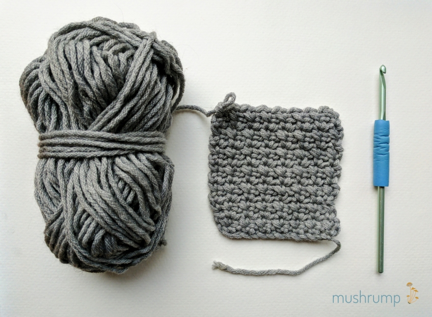 gray yarn skein, crocheted square in a textured stitch, and pale green crochet hook with blue grip, all on white background