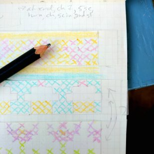 A portion of a graph-paper notebook with multi-colored designs in it: hearts, cupcakes, and flowers. A black pencil is resting on the notebook, and some pattern words are at the top.