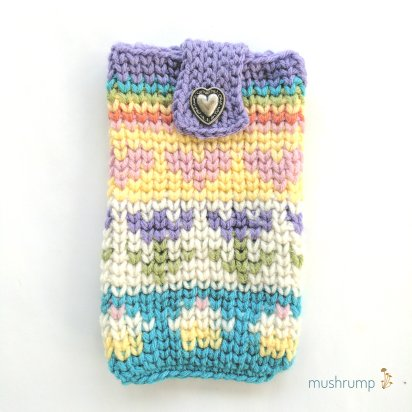 A crocheted pouch on a white background with a logo in the bottom right corner that says Mushrump and has yellow mushrooms next to it. The pouch looks knit and has pastel hearts, flowers, cupcakes, and a rainbow on it. There is a metal heart button near the top.